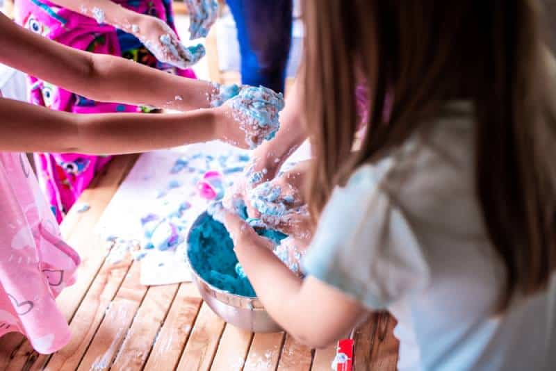children make a mess with frothy slime at a birthday party