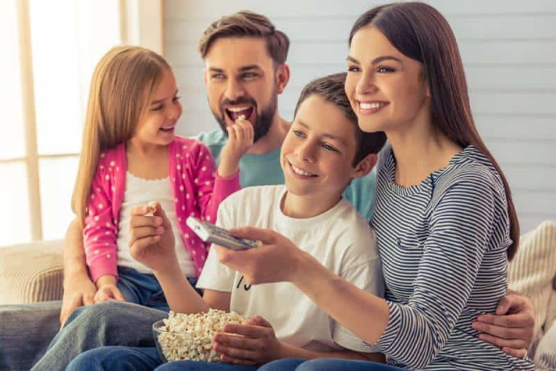 young parents, their daughter and son are watching TV, eating popcorn and smiling
