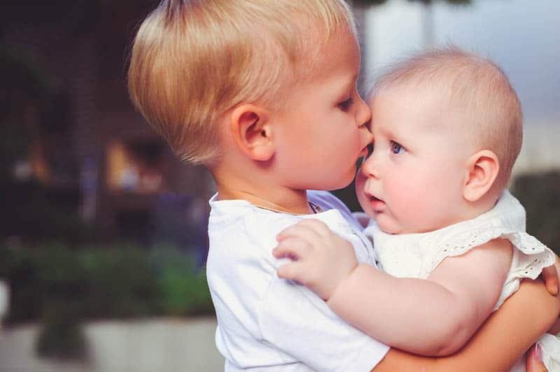 siblings  kissing each other