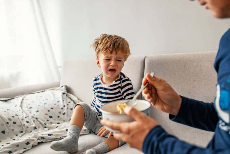 child refusing to eat at home with white background while father is trying to deceive the toddler by tricks