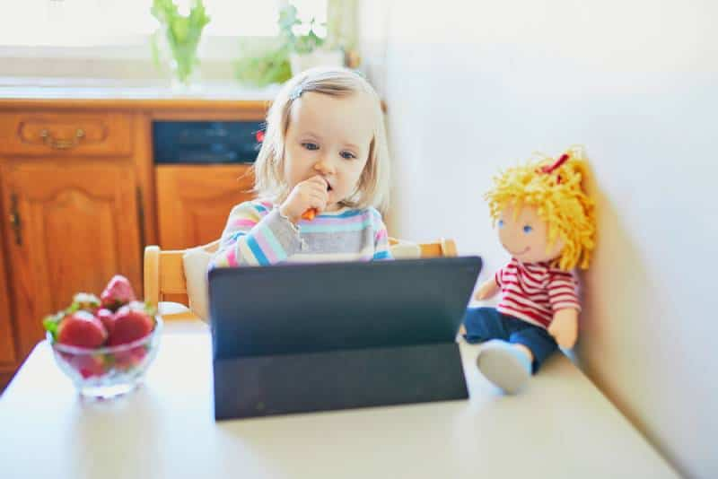 toddler girl eating fresh strawberries and using tablet at home
