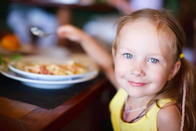 adorable little girl in yellow shirt having lunch