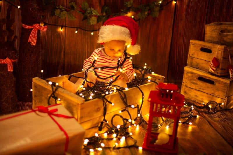 Cute child in Santa Hat sitting in box and playing with Christmas lights
