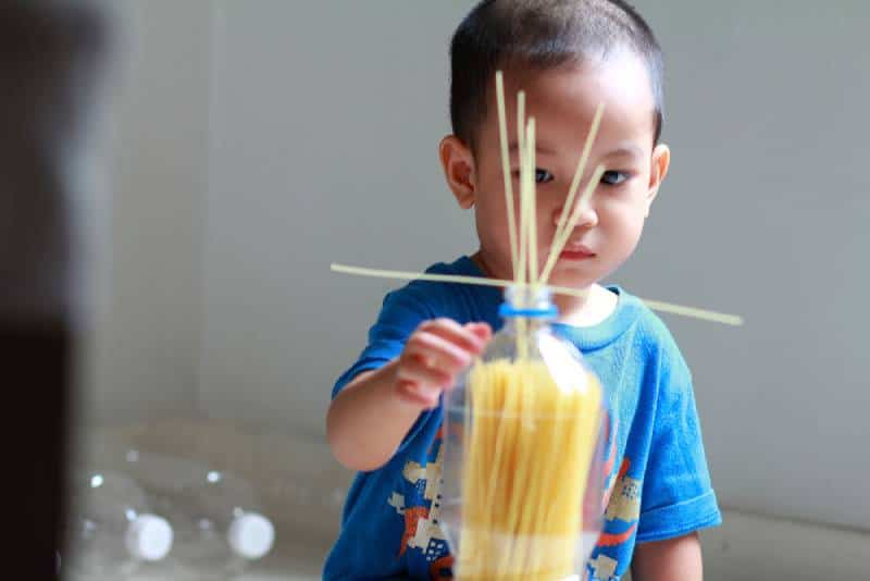 Boy focus on the pasta while he put it in bottle