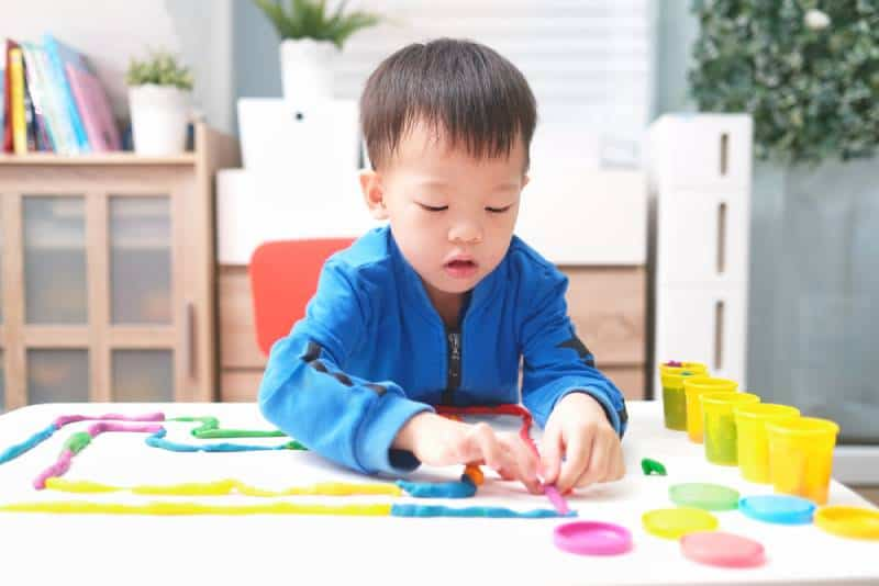child having fun playing colorful modeling clay at a table
