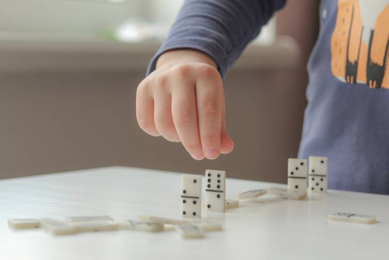Kid playing with dominoes on white table