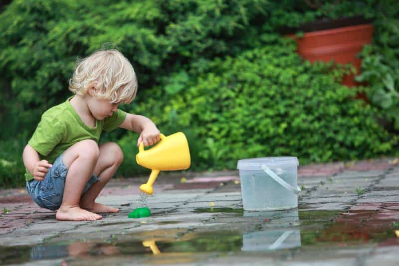 White little barefoot girl playing with water outdoors