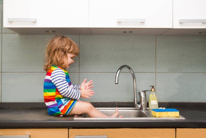 toddler girl in a colorful dress washes her hands and playing with foam in the sink in a kitchen