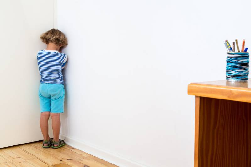 Kid in blue shirt and shorts standing in the corner