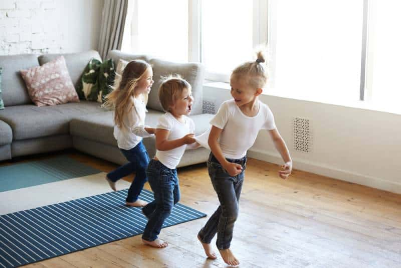 three happy joyful children one girl and two boys pullin each other by clothes while dancing at home