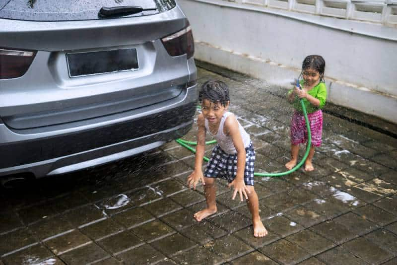Little girl playing a water hose while washing a car with her brother at home