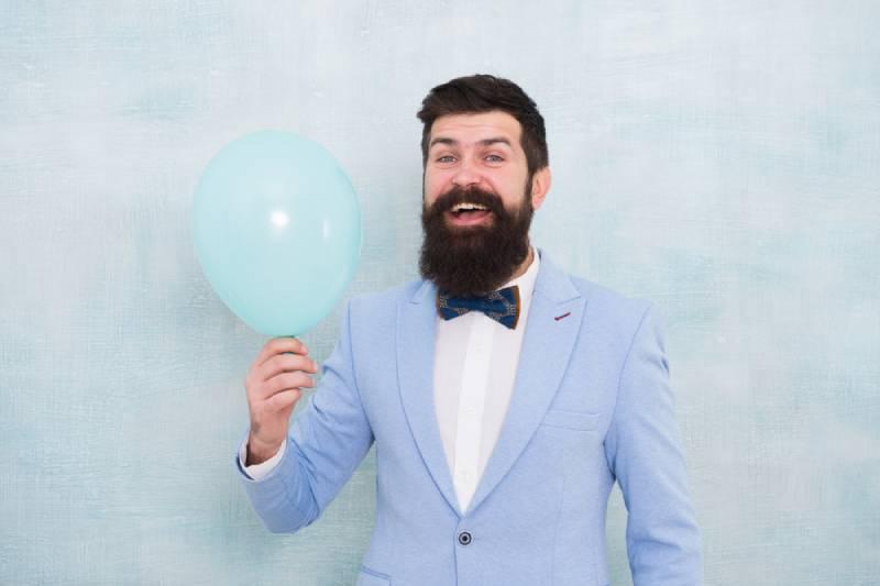 Man in blue tuxedo holding a balloon