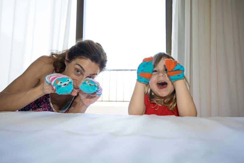Mom and kid making sock puppets and having fun at home