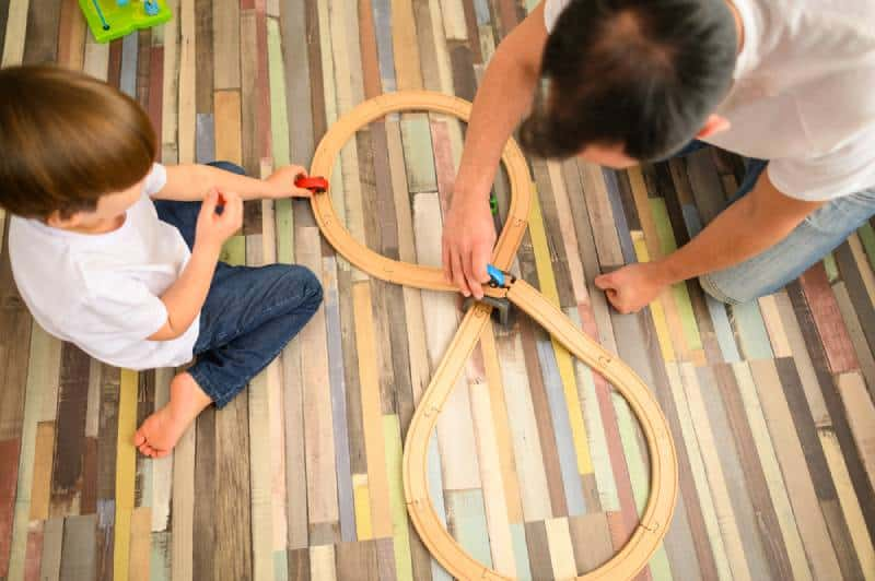 Child and father playing with race track at home