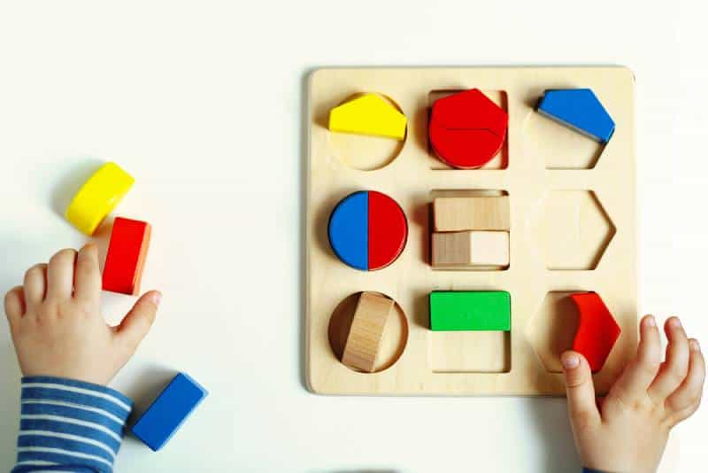little Montessori kid learning about color, shape, sorting, arranging by engaged colorful wooden sensorial blocks