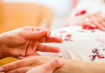 Midwife setting pregnant woman acupuncture needle