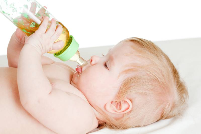 adorable blond child drinking from bottle