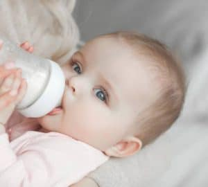 mother feeding her little cute baby daughter with bottle of child formula