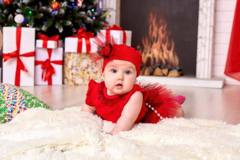 baby child under one year old lies on the background of the Christmas tree and gifts