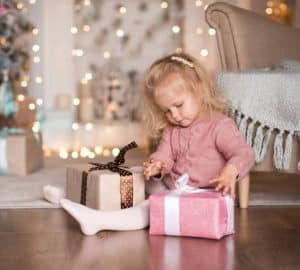 3 year old girl open Christmas present sitting on floor in room over Christmas decor