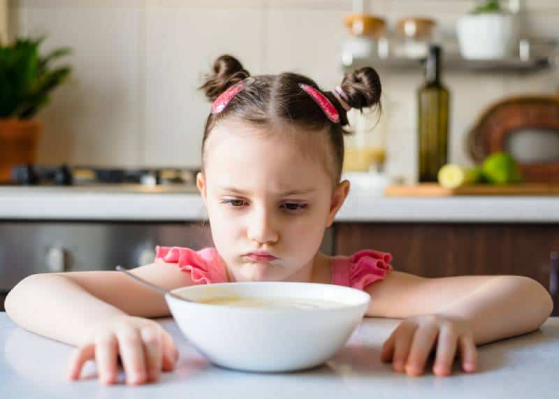 Kid Girl doesn't want to eat vegetable puree soup in kitchen