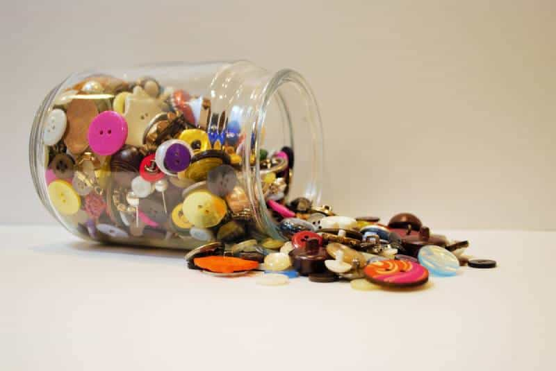 jar full of multi colored buttons overflowing and spilling out