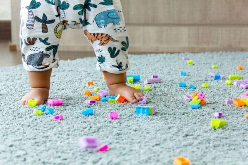 Baby legs on a rug among kids bricks in a kindergarten