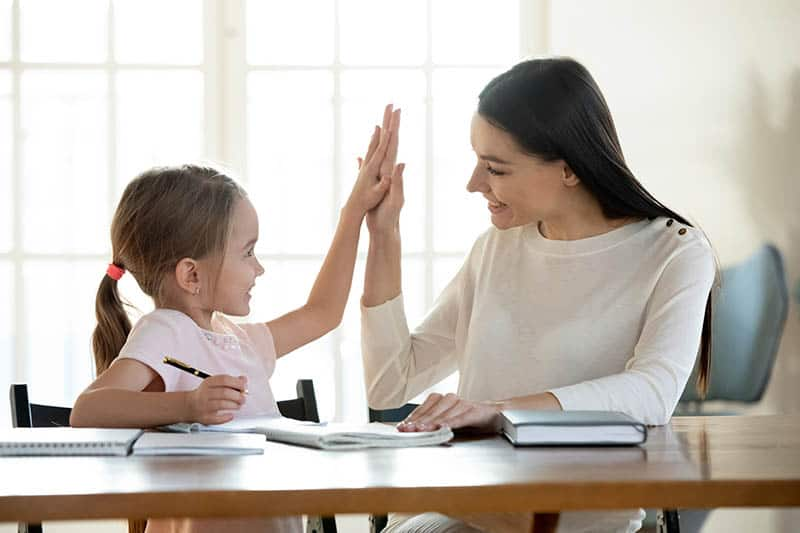 mother praising daughter for doing a good job doing homework