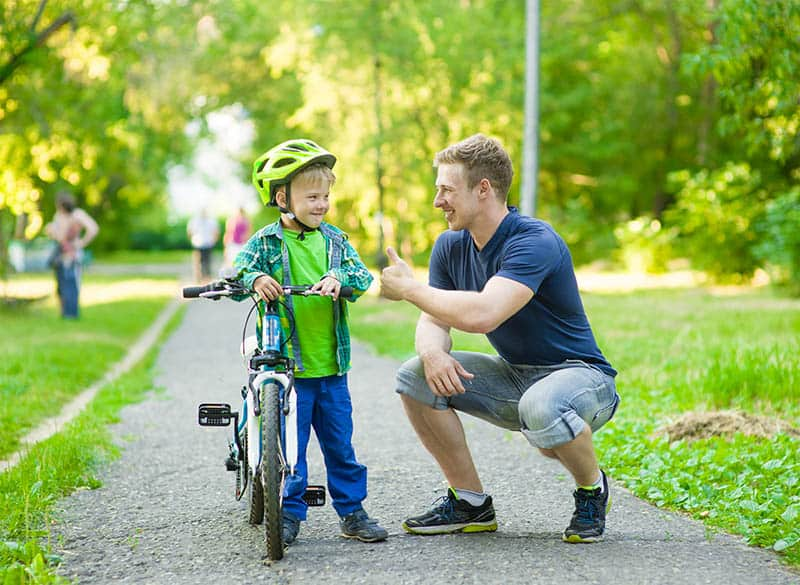 father and son enjoying a nice day outside in the park kid learning how to ride a bike