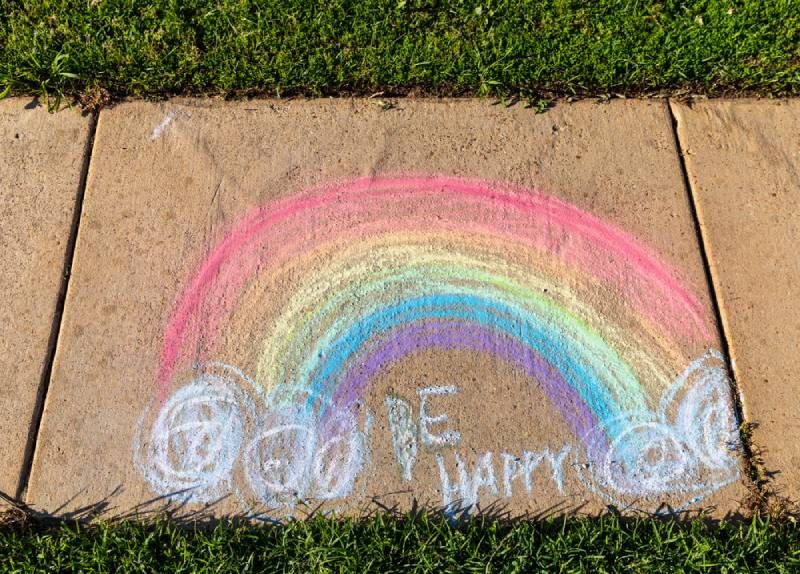 "The words ""Be Happy"" written with sidewalk chalk"