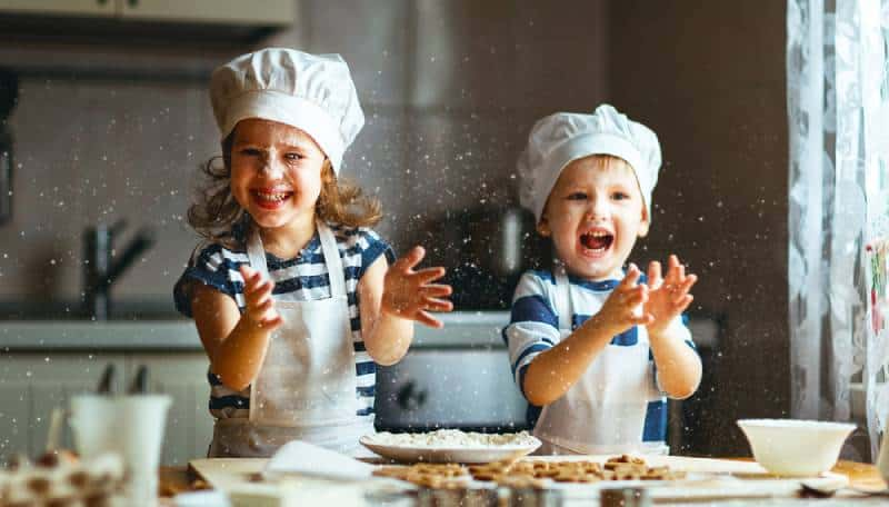 funny kids are preparing the dough, bake cookies in the kitchen