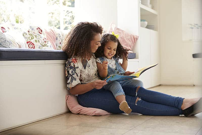 mother and daughter sitting on floor reading a book rie parenting method
