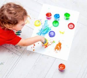 A child is playing with paints on the floor at home