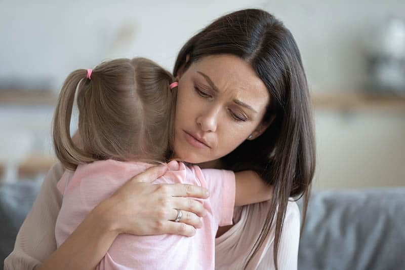 worried single mother hugging daughter