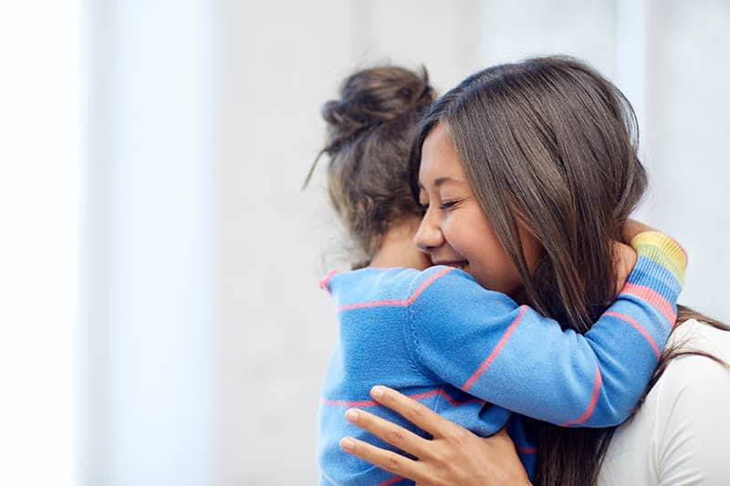 asian single mother hugging child