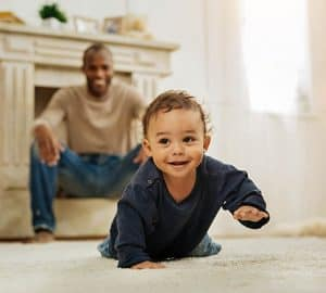 baby crawling in living room with back father in background