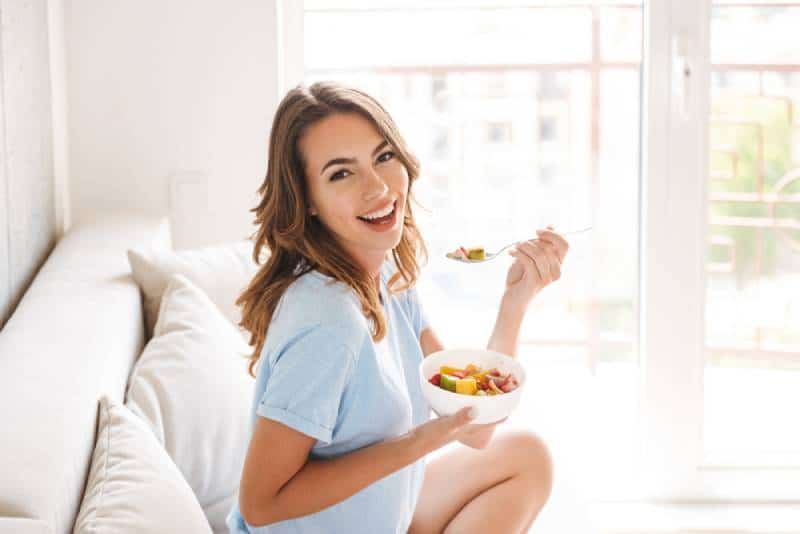 woman eating healthy breakfast while sitting on a couch at home