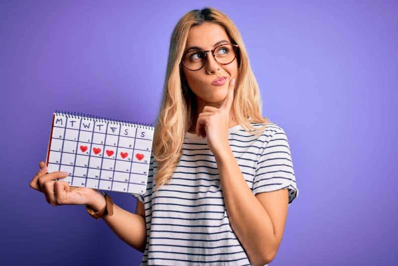 blonde woman holding period calendar to control menstrual cycle on purple background