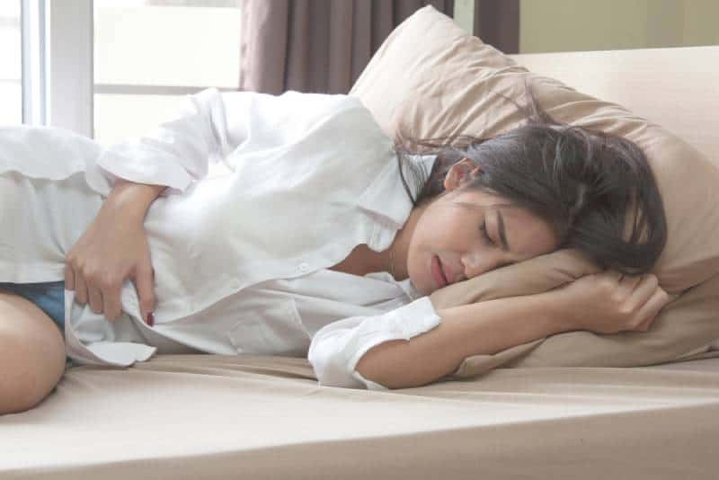 woman in bed with stomach pain