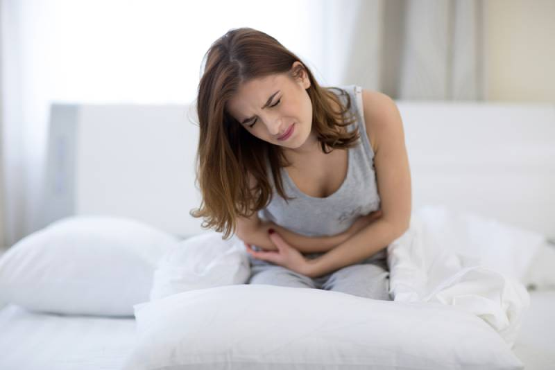 Young woman sitting on the bed and holding her stomach with pain