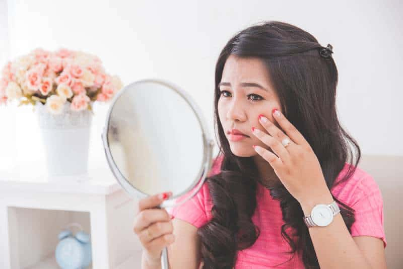 Woman holding a mirror, touch and worrying about her face