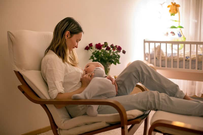 woman breastfeeding baby on the nursery glider