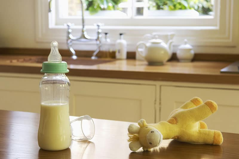 baby bottle with milk and a toy on the table in the kitchen