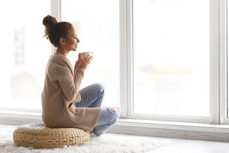 beautiful young woman drinking coffee and looking through window