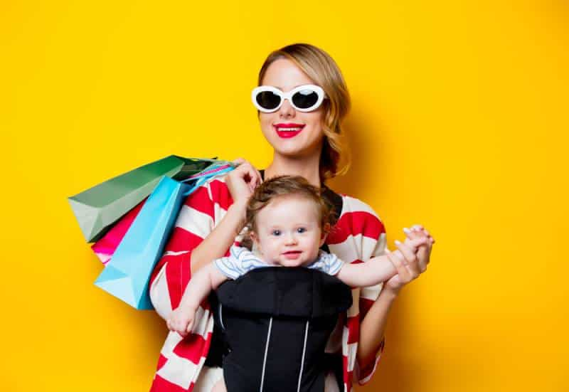 Mother and little baby in carrier have a shopping with bags on yellow background