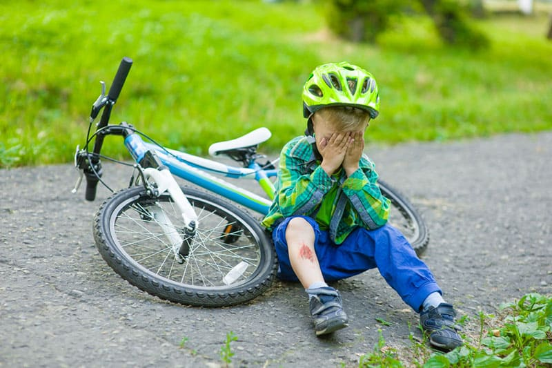 crying child sitting on the floor after falling from a bike
