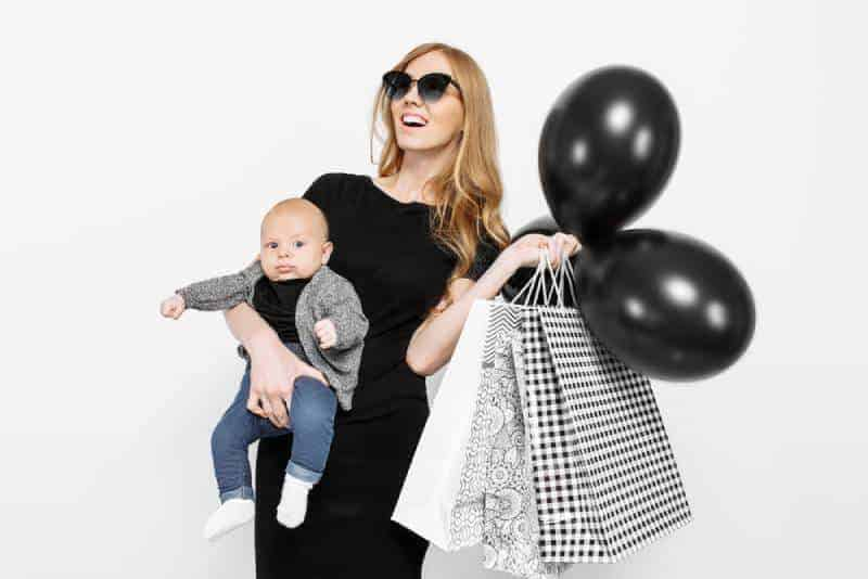 mom holding a baby and shopping bags with baloons