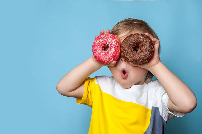 young boy playing with donuts