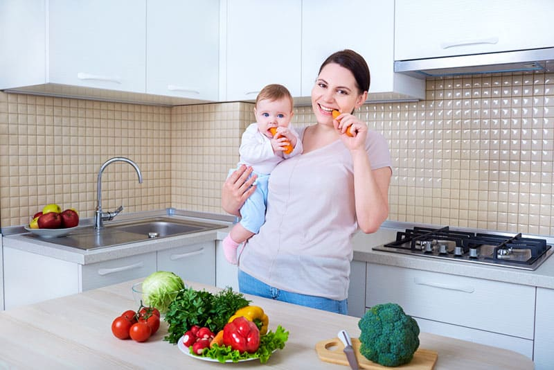 happy mother and baby eating a carrot in the kitchen