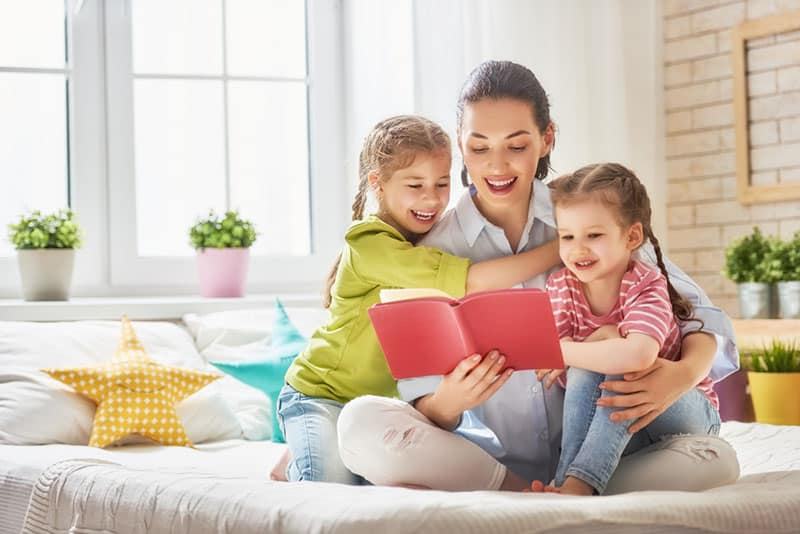 happy mother reading to her little daughters